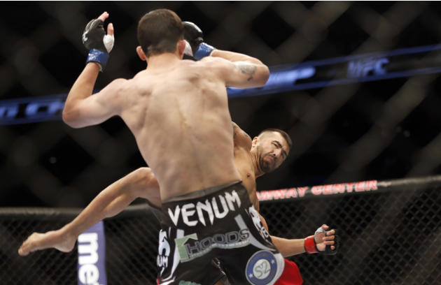 Estevan Payan, right, and Alex White fight in a mixed martial arts event on Saturday, April 19, 2014, at UFC Fight Night in Orlando Fla.. White won. (AP Photo/Reinhold Matay)