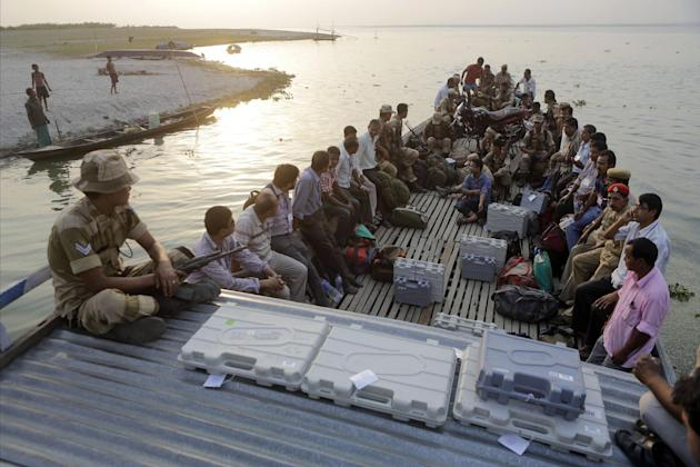 Election officers sit on a boat with electronic voting machines, guarded by security personnel as they travel to their assigned polling stations, on the River Brahmaputra on the eve of voting near Fat