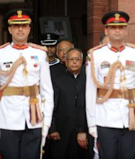 India's new President Pranab Mukherjee (C) is escorted by presidential bodyguards as he arrives for his swearing-in ceremony at parliament in New Delhi on July 25, 2012