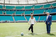 This picture released by the Brazilian Presidency showing President Dilma Rousseff (L) next to Bahia governor Jacques Wagner while she gives the kick off during the inauguration of the Fonte Nova Arena in Salvador, Bahia State on April 5, 2013