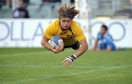 Australia's Nick Cummins scores a try during their Six Nations rugby union match against Italy at the Olympic stadium in Turin