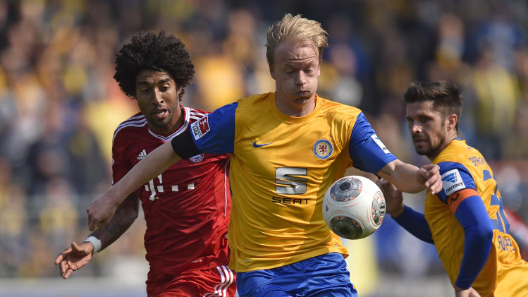 Braunschweig's Bjoern Kluft, right, and Bayern's Dante of Brazil challenge for the ball during the German Bundesliga soccer match between Eintracht Braunschweig and Bayern Munich in Braunschweig, Germany, Saturday, April 19, 2014