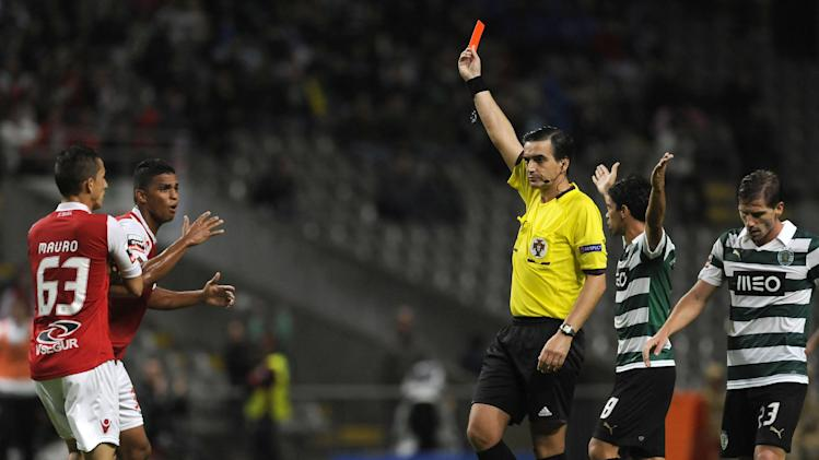 Sporting Braga's Aderlan Santos, second left, from Brazil receives a red card from referee Paulo Baptista after tackling Sporting's Fredy Montero, on the pitch, from Colombia, during their Portuguese League soccer match at the Municipal Stadium, in Braga, Portugal, Saturday Sept.. 26, 2013
