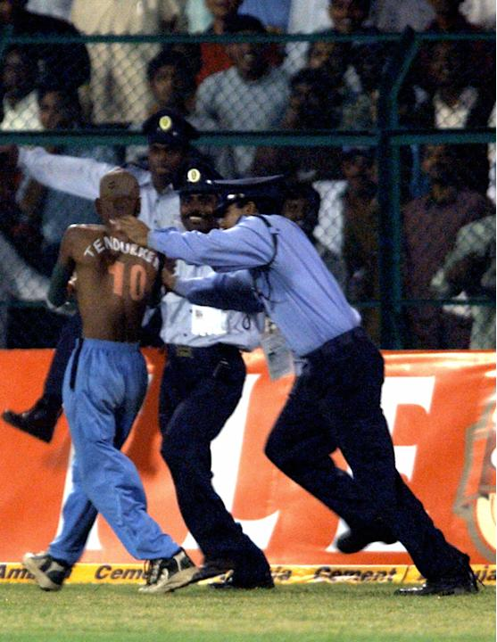 Security personnel arrest a fan of India