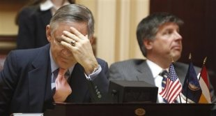 Virginia state Senate Republican leader Thomas Norment, left, puts his head in his hand as he listens to debate on a bill requiring an ultrasound before an abortion in Richmond, Virginia, on Tuesday. The measure passed, 21 to 19. (AP Photo/Steve Helber)