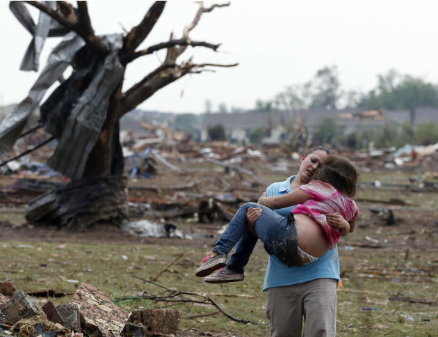A woman carries a child through a field near the collapsed Plaza Towers Elementary School in Moore, Okla., Monday, May 20, 2013. The relationship between the woman and the child was not immediately kn