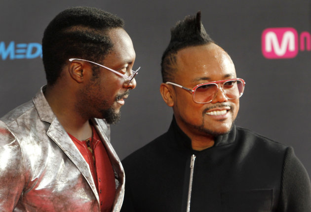 Will.i.am, left, and apl.de.ap of the Black Eyed Peas pose on the red carpet at the 2011 Mnet Asian Music Awards in Singapore on Tuesday, Nov. 29, 2011. (AP Photo/Terence Tan)