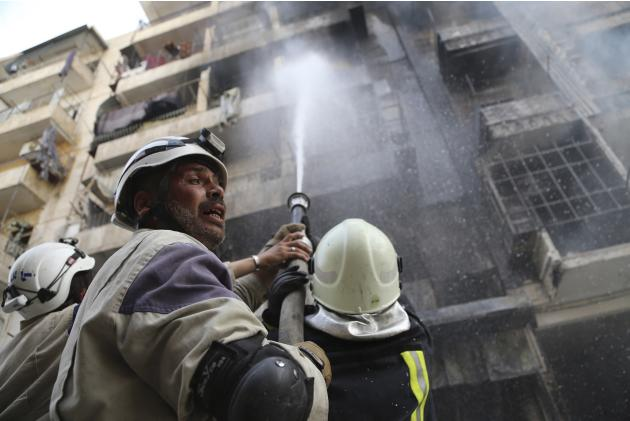 Firefighters try to put out a fire at a site hit by what activists said were barrel bombs dropped by forces loyal to Syria's President Bashar al-Assad in Aleppo's al-Shaar district