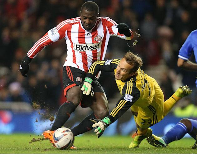 In this Dec. 17, 2013, file photo, Sunderland's Jozy Altidore, left, hits a shot toward goal past Chelsea's goalkeeper Mark Schwarzer, right, during an English League Cup quarterfinal soccer m