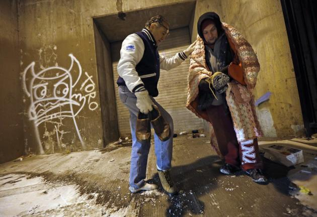 Doctor Angelo hands over the shoes off his feet to help a homeless man under the overpasses on Lower Wacker Drive in Chicago