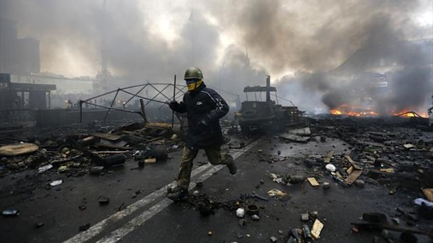 An anti-government protester runs ttrough the streets of Kiev in Ukraine after violent clashes