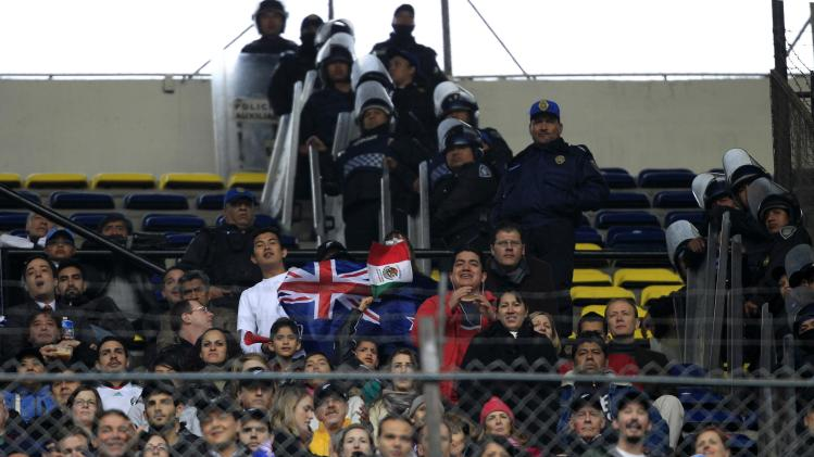Police officers stand guard next to fans during a soccer match between Mexico and New Zealand, in Mexico City