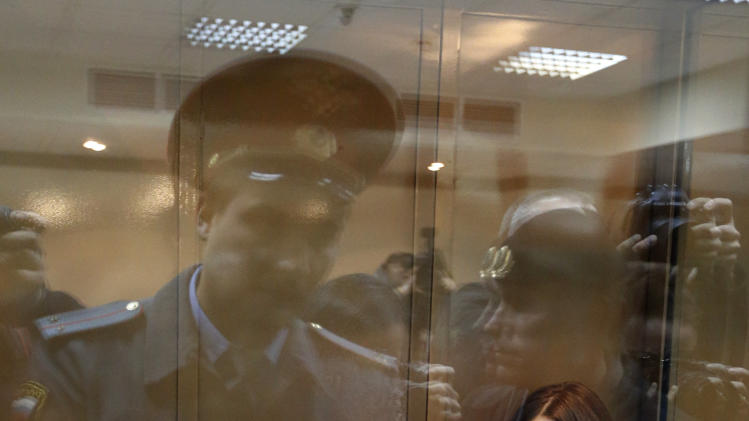 FILE - In this Monday Oct. 1, 2012 file photo, feminist punk group Pussy Riot members, from left, Maria Alekhina, Yekaterina Samutsevich and Nadezhda Tolokonnikova sit in a glass cage at a court room in Moscow, Russia. Alekhina went on hunger strike Wednesday, May 22, 2013, in protest at not being allowed to attend her own parole hearing in Perm province. In letters dated Monday and posted online by the group's supporters, McCartney asks for parole to be granted to Maria Alekhina and Nadezhda Tolokonnikova, currently serving two-year sentences for an impromptu protest in Moscow's main cathedral. The judge in Mordovia province to whom the Beatles frontman Paul McCartney addressed two letters in Pussy Riot support, denied Tolokonnikova parole last month. (AP Photo/Sergey Ponomarev, file)