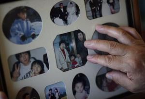 Watanabe touches a photograph of his late wife Hamako, …