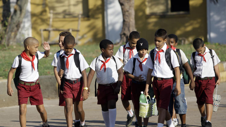 Boys in uniform walk to school in Santiago de Cuba, Cuba, Monday, Nov. 5, 2012. Classes resumed Monday in a sign of some return to normalcy, but more than 100 schools remain shuttered due to storm damage.  (AP Photo/Ismael Francisco, Cubadebate)