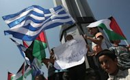 "Palestinian children wave Palestinian and Greek flags during a rally in Gaza City. Greece tried to appease furious activists after halting a flotilla bound for Gaza, offering to deliver aid ""through existing channels"" and reaching out to the Palestinian Authority Sunday"