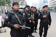 Rapid Action Battalion (RAB) personnel stand guard during a nationwide strike in Dhaka on February 18, 2013. Police firing rubber bullets shot dead a protester in demonstrations in eastern Bangladesh as a strike called by the largest Islamist party paralysed life across the nation