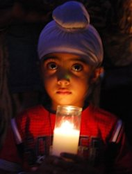 Akandeep Delam, 4, holds a candle on Monday at a vigil honouring six people killed in an attack on a Wisconsin Sikh temple the day before. A small US community struggled to understand Tuesday how a racist former soldier with links to white supremacists acted on his hatred and shot dead six unarmed people at a suburban Sikh temple