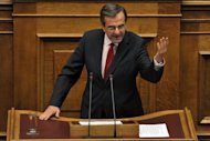 Greek Prime Minister Antonis Samaras gives a final speech at the Greek parliament in Athens. The coalition government of Samaras won a largely symbolic confidence vote on Sunday, picking up a comfortable mandate to tackle the country's two-year-old crisis