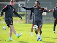 Manchester United's Patrice Evra (R) and Wayne Rooney during a team training session on October 1. Two defeats in six league games have left United four points off the pace in the league and dented confidence ahead of their trip to Romania's Cluj