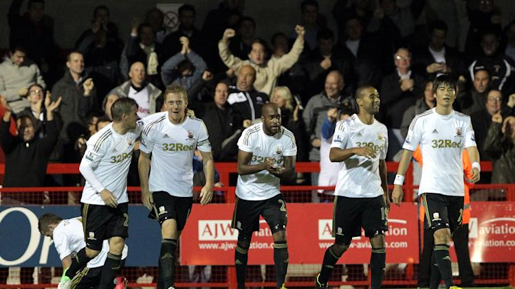 Swansea players celebrate Garry Monk's (second left) winning goal against Crawley