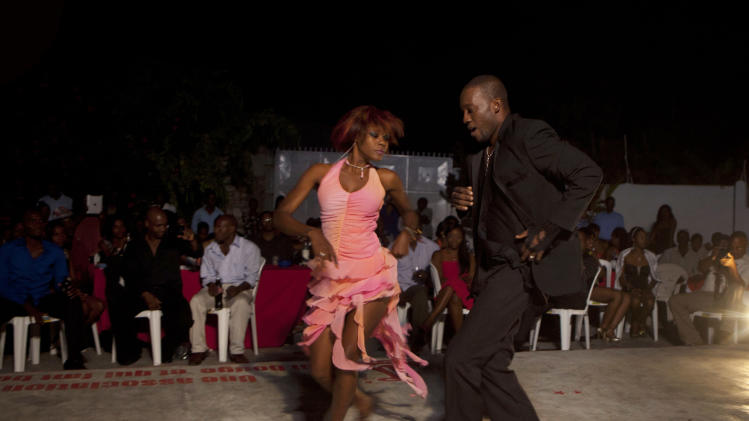 In this Jan. 20, 2013 photo, professional dancer Georges Exantus, right, performs with Modeline Gene Arhan during a show in Port-au-Prince, Haiti. Exantus thought he'd never dance again. The earthquake three years ago in Haiti's capital flattened the apartment where he was living where he spent three days trapped under a heap of jagged rubble. After friends dug him out, doctors amputated his right leg just below the knee. Three years later, the 32-year-old professional dancer is back on the floor, spinning away as he does the salsa, cha-cha and samba. A prosthetic leg doesn't hold him back. (AP Photo/Dieu Nalio Chery)