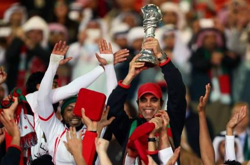 Emirati coach Mahdi Ali raises the trophy after his team won the final of the 21st Gulf Cup on January 18, 2013 in Manama. United Arab Emirates won 2-1 against  Iraq.  AFP PHOTO/MARWAN NAAMANI
