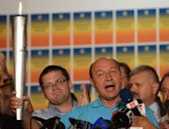 Romanian President Traian Basescu holds The Democracy Torch as he addresses reporters at his electoral campaign headquarters in Bucharest. Basescu escaped impeachment Monday when a referendum on his removal from office fell short of the 50 percent turnout threshold, despite a resounding vote for his dismissal