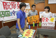 In this Friday, July 22, 2011 photo, Ehime University students, from left, Ryouichi Matoba 23, Shunichi Muranaka, 21, and Megumu Sakai 21, hold anti-nuclear signs during an interview in Matsuyama, population 500,000, that sits 30 miles (50 kilometers) from Ikata, one of the world's most seismologically risky plants in western Japan. Many in Japan have grown uneasy with nuclear power since the March 11, 2011 tsunami, which sent the Fukushima Dai-Ichi plant into meltdown. Yet six months after the disaster, Japan seems to feel it has little choice but to live with nuclear power, at least for now. (AP Photo/Koji Sasahara)