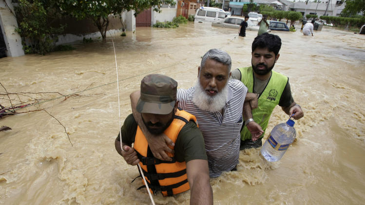 Pakistani soldiers rescue a resident from an area flooded by heavy rains on the outskirts of Karachi, Pakistan, Sunday, Aug. 4, 2013. Heavy rains that swept across Pakistan brought down more than 100 homes and caved in a factory wall, killing at least a dozen people in the downpours, officials said. (AP Photo/Fareed Khan)
