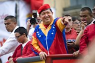 Venezuelan President Hugo Chavez (C) waves to supporters before registering his candidacy in the National Electoral Center for the upcoming presidential election, in Caracas on June 11, 2012. Thousands of followers took to the streets of Caracas supporting his candidacy