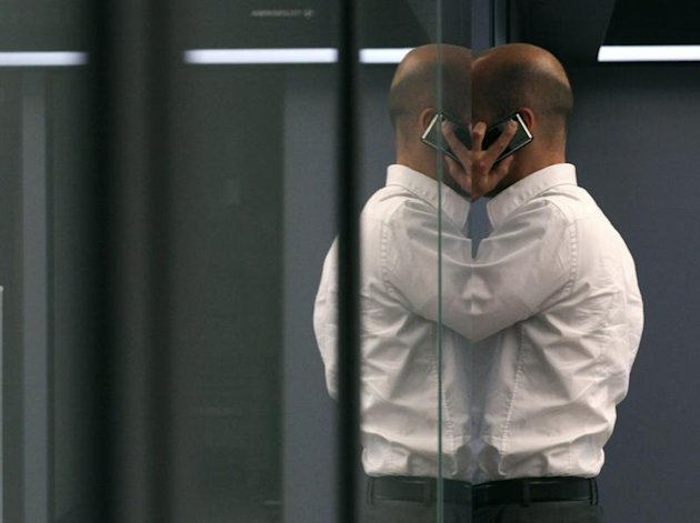 A bourse trader uses a cell phone during a trading session at Frankfurt's stock exchange. (Reuters)