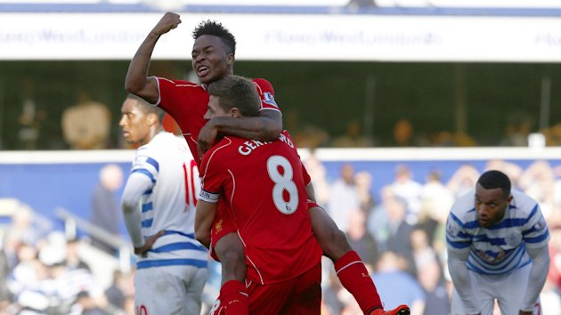 Liverpool's Raheem Sterling (REAR) celebrates with Steven Gerrard after his cross was deflected into the goal by QPR's Steven Caulker (Reuters)