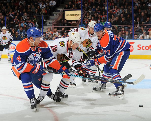 EDMONTON, AB - NOVEMBER 18: Taylor Hall #4 and Oscar Klefbom #77 of the Edmonton Oilers battle for the puck against Jonathan Toews #19 of the Chicago Blackhawks on November 18, 2015 at Rexall Place in Edmonton, Alberta, Canada. (Photo by Andy Devlin/NHLI via Getty Images)