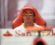 "Ferrari driver Fernando Alonso relaxes in the pit during the third practice session of the Formula One Japanese Grand Prix at the Suzuka circuit on October 6. The Spaniard admitted he'd been pitched into a ""mini-championship"" after a mistake from Kimi Raikkonen shattered his big lead in the Formula One standings"