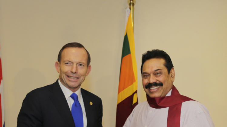 Australia's PM Abbott, who is currently in Sri Lanka to attend the CHOGM 2013, gives Sri Lanka's President Rajapaksa a signed Australian Rugby Union jersey in Colombo