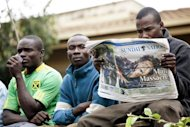 A man reads a daily newspaper with other onlookers at the edge of a security perimeter put into place near the Westgate shopping centre where gunmen are holding hostages, in Nairobi September 22, 2013. REUTERS/Siegfried Modola