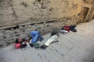 Homeless men sleep on the roadside in the old part of Kabul