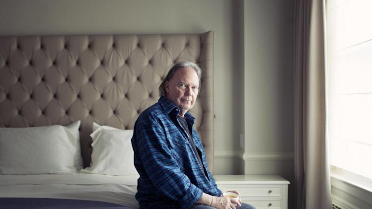 "This Sept. 27, 2012 photo shows singer-songwriter Neil Young posing for a portrait at The Carlyle hotel in New York. Young has released his first book, a memoir titled, ""Waging Heavy Peace."" (Photo by Victoria Will/Invision/AP)"