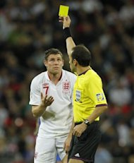James Milner of England is shown the yellow card by Turkish referee Cuneyt Cakir (R) during the 2014 World Cup qualifying football match against Ukraine at Wembley Stadium in north London. The match ended in a 1-1 draw
