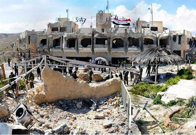 This Monday, April 14, 2014 photo, released by the Syrian official news agency SANA, shows Syrian government soldiers gathering outside a damaged hotel that Syrian rebels had been using, in Maaloula v