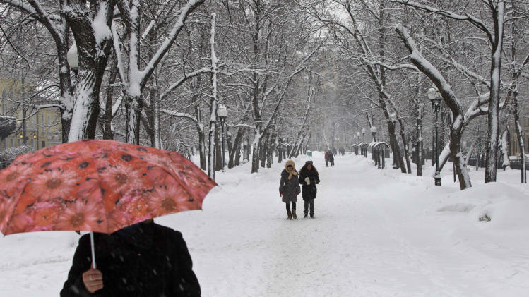 People walk along a snow-covered boulevard in Moscow, Russia, Friday, March 15, 2013. A heavy snowfall has continued for the second day in Moscow with temperatures hovering around 0 degrees Celsius (32 Fahrenheit). (AP Photo/Misha Japaridze)