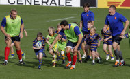 French rugby players play rugby with boys from the Takapuna rugby club after a training session, in Auckland, New Zealand, Tuesday, Sept. 27, 2011. France will play Tonga in their next Rugby World Cup match on Saturday, Oct. 1 in Wellington. (AP Photo/Christophe Ena)