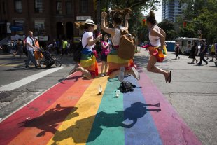 Pride festival revelers jump on a rainbow painted crosswalk on Church Street in Toronto' LGBT neighbourhood. (CANADA - Tags: SOCIETY TPX IMAGES OF THE DAY)