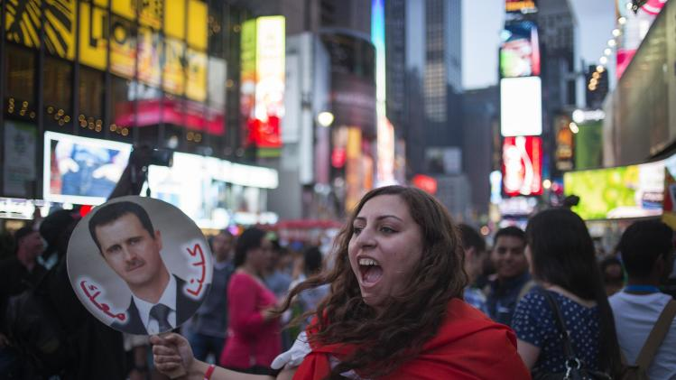 Syrian-American woman and supporter of Syrian President al-Assad, who arrived in Times Square to take part in an anti-war rally, shouts at a group of Syrian-Americans against Assad's government in Midtown Manhattan
