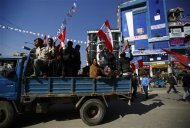 Supporters of Nepali Congress Party in a vehicle cheer for their party as Constituent Assembly Election scores are displayed on a screen outside the Constitution Assembly Building in Kathmandu November 21, 2013. REUTERS/Navesh Chitrakar