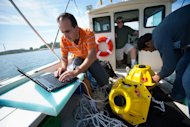 Electrical engineering graduate students Hovannes Kulhandjian and Zahed Hossain test a wireless underwater Internet in Lake Erie.