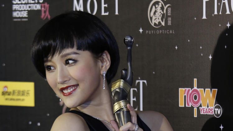 "Hong Kong actress Dada Chan poses for photographers after winning the Best Supporting Actress award for her role in the movie ""Vulgaria"" at the 32nd Hong Kong Film Awards in Hong Kong Saturday, April 13, 2013. (AP Photo/Vincent Yu)"