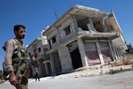 A Rebel walks in front of a destroyed building in the village of Al-Rami, in the northwestern Syrian province of Idlib, on June 22, 2013
