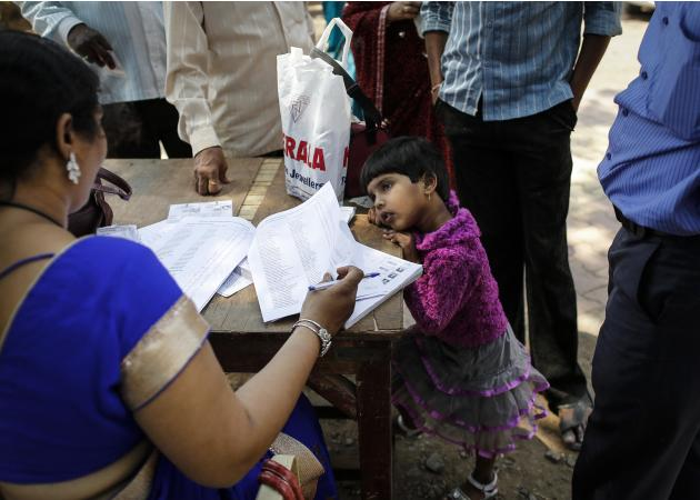Girl looks at polling officer as her father waits to cast his vote at a polling station in the village of Vadgaon, in the western Indian state of Maharashtra